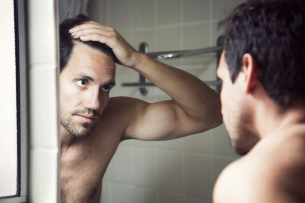 hairline-baldness-man-mirror-brown-hair-early-signs-balding-viviscal-blog