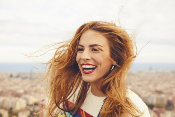 redhead woman happy laughing copper red choosing fall hair color viviscal hair blog