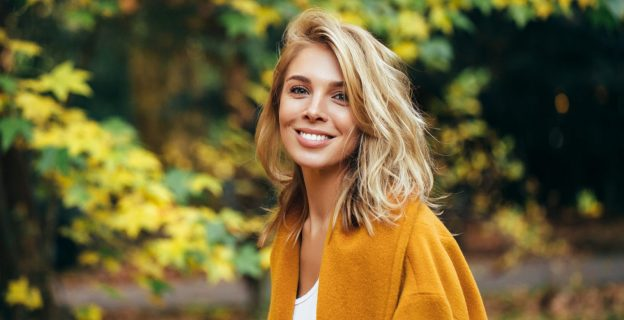 autumn-hair-blonde-woman-leaves-orange-coat-choosing-a-new-hair-color-fall-viviscal-blog
