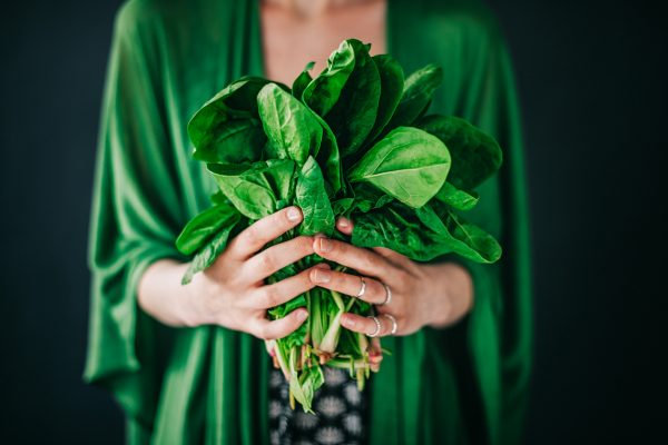 woman holding leafy green vegetables best foods for thicker healthier hair viviscal blog