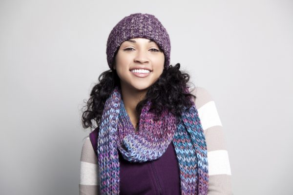 curly hair black purple winter hat smiling perfecting a winter beanie hairstyle viviscal hair blog