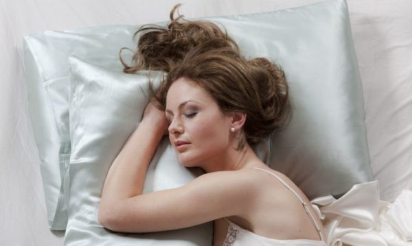woman sleeping silk pillowcase how to tame frizzy hair viviscal hair blog