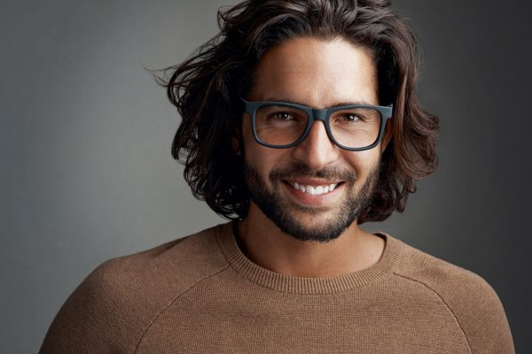 man glasses brown hair smiling dark background flow long haircut hot 2019 hairstyles for men viviscal hair blog