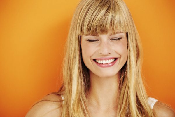 Young blond woman orange background bangs square face choosing a hairstyle for your face shape viviscal hair blog