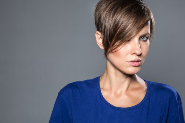 short hair woman blue shirt pixie cut side swept bangs heart shaped face choosing a hairstyle for your face shape viviscal hair blog