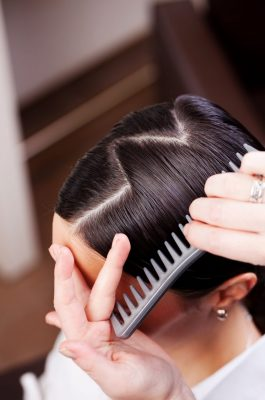 Combing womans dark hair with a zig zag part viviscal blog