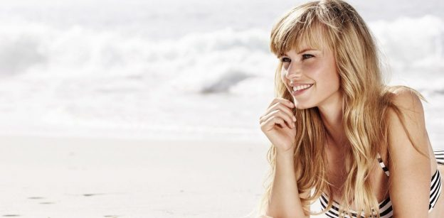 smiling young blond woman beach summer hair care tips viviscal hair blog