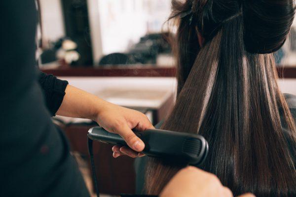 woman salon flat iron how does chemical hair straightening work? viviscal hair blog