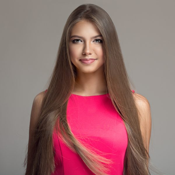 woman long straight shiny brown hair pink shirt smiling how does chemical hair straightening work viviscal hair blog