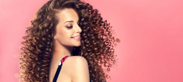 smiling woman side pink background long curly permed hair the perm should you consider hair perming? viviscal hair blog
