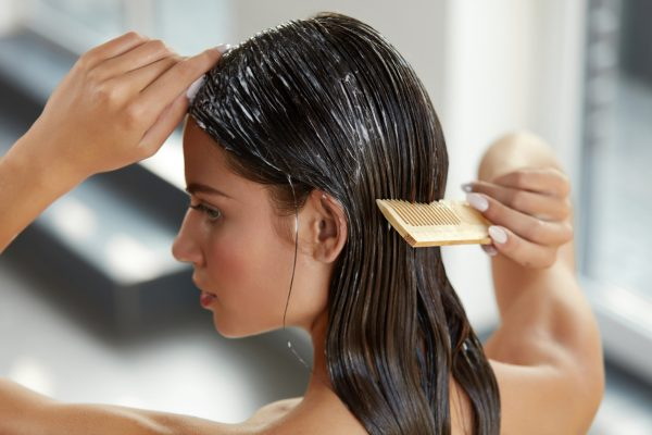 Woman combing hair product after shampoo best products for fine hair viviscal hair blog