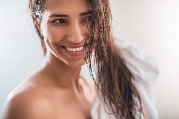 smiling woman towel drying wet hair dry gently how to look good with air dried hair viviscal hair blog