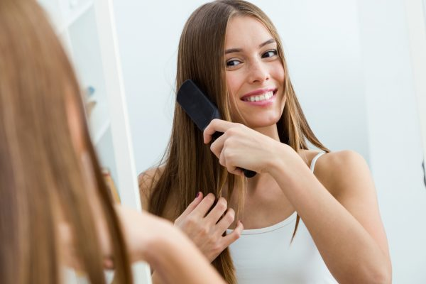 smiling woman brushing long hair mirror tips for using dry shampoo viviscal hair blog
