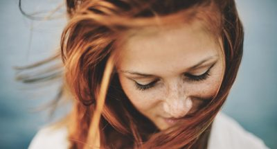 smiling woman looking down red hair find your perfect red hair color viviscal hair blog