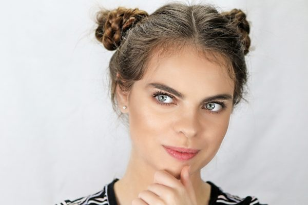 woman closeup brown hair space buns double cute back to college hairstyles viviscal hair blog