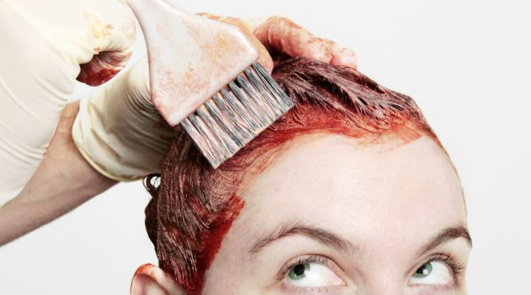 applying messy red hair dye woman closeup looking up cautious at home hair dye tips tricks viviscal hair blog