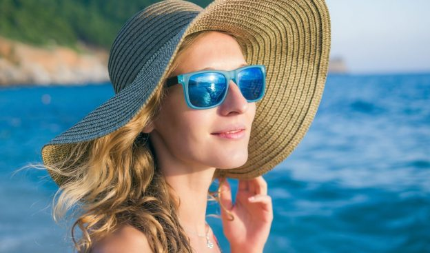 woman blonde wavy hair beach hat blue sunglasses getting perfect the beach wave curls viviscal hair blog