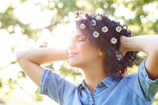 daisies fresh flowers woman outside brown curly hair our favorite festival hairstyles viviscal hair blog