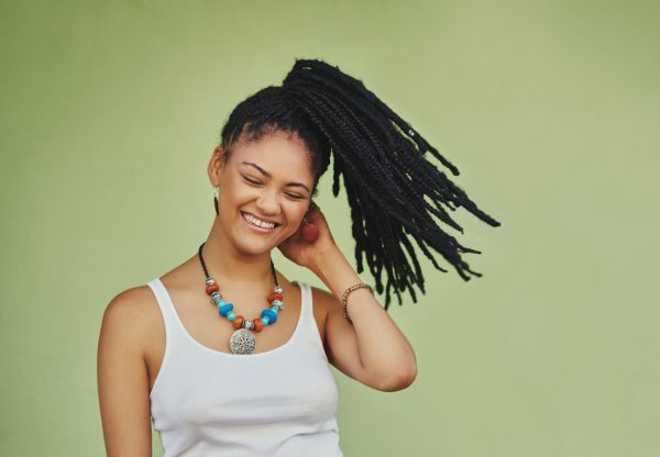 cute back to college hairstyle on an african american woman who happily smiling flipping her high ponytail full of braids against a green background viviscal hair blog
