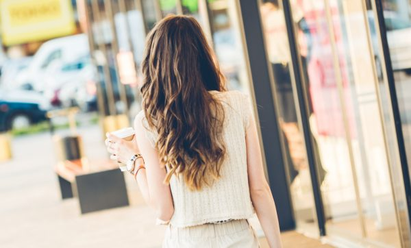 woman back long wavy hair walking street holding coffee cup getting the perfect beach wave curls viviscal hair blog