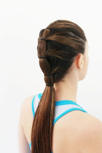 A brunette woman from behind shows her sporty hairstyle, a tiered ponytail.