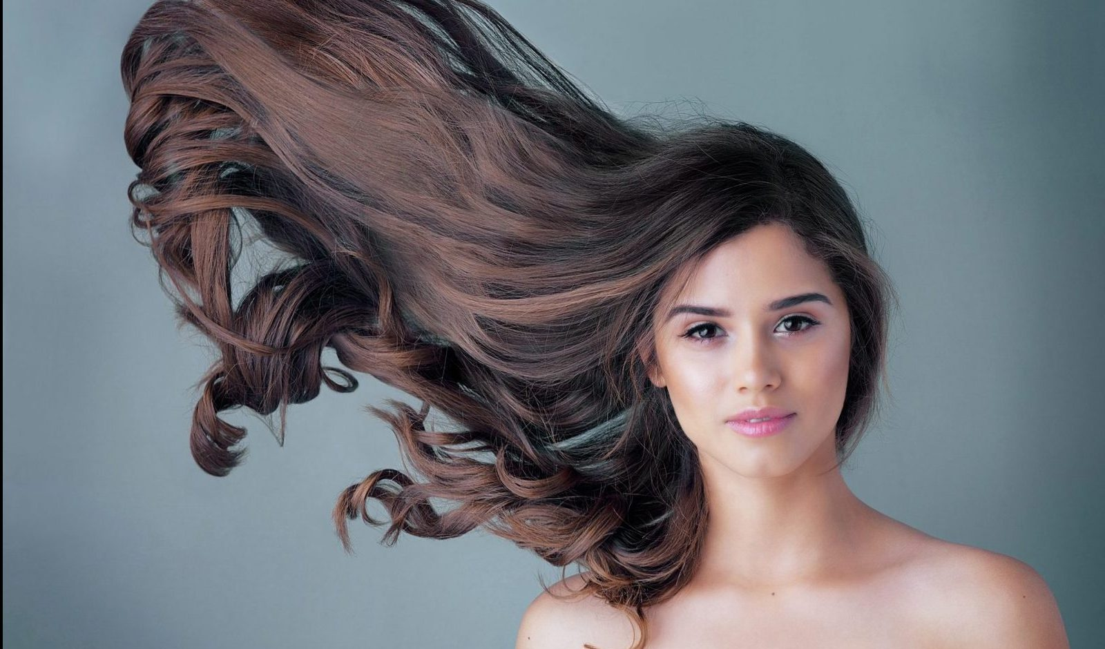 woman long brown healthy hair in the air motion gray blue background what are the best vitamins for hair growth viviscal hair blog