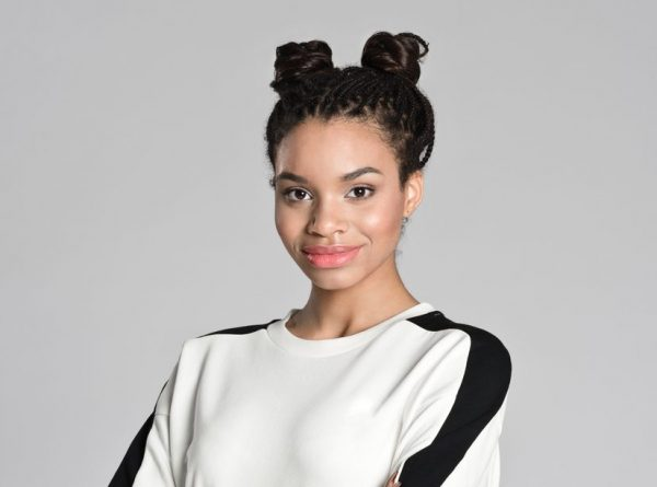 A black woman smiles at the camera. She is wearing a sporty hairstyle, with two buns on top of her head, and a black and white shirt.