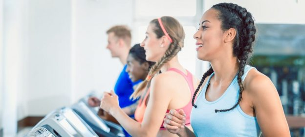 Three women with sporty hairstyles workout on treadmills. A man is working out in the background.