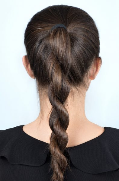 A brunette woman from behind wears a sporty hairstyle, a high-ponytail rope braid.