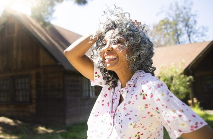 laughing african american woman gray hair curly does hair texture change with age? viviscal hair blog