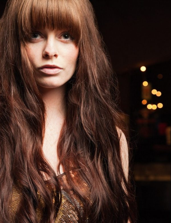 woman long red shag layered hair bangs fringe close cropped dark background best haircut for thin long hair viviscal hair blog