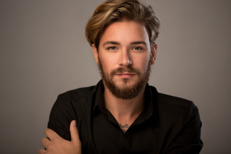 closeup man flow hairstyle blonde hair beard gray background how often should males get a haircut? viviscal hair blog