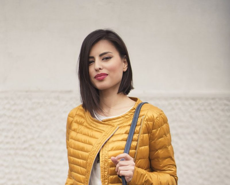 smiling woman dark black hair yellow jacket long bob haircut best haircuts for thin long hair viviscal hair blog