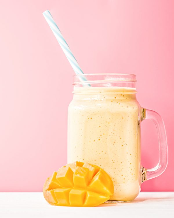 mango fruit smoothie mason jar straw pink background mango strawberry smoothie healthy hair growth smoothies viviscal hair blog