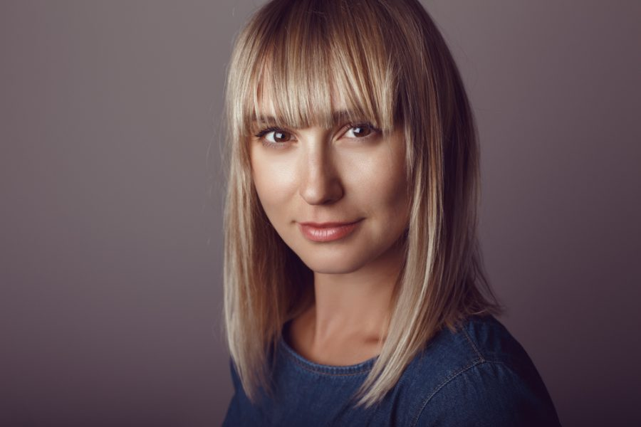 woman blonde blunt shoulder length hair bangs dark gray background best haircuts for thin long hair viviscal hair blog