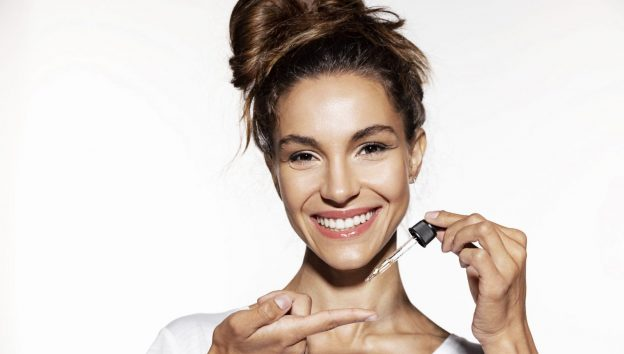 woman smiling holding oil dropper lavender oil benefits for hair viviscal hair blog