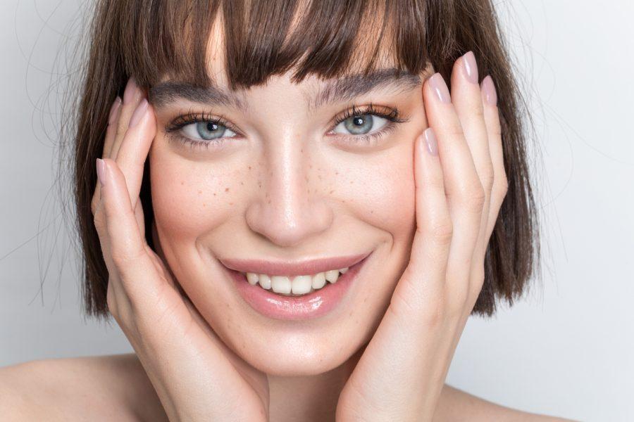 closeup woman dark hair freckles smiling wispy bangs for thin hair viviscal hair blog