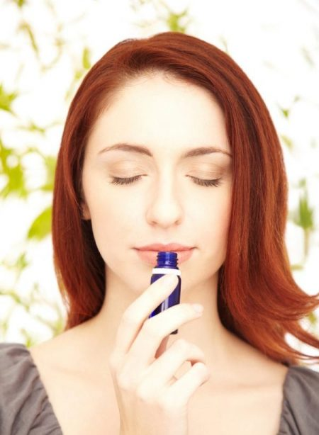 closeup of a relaxed redhead woman smelling lavender