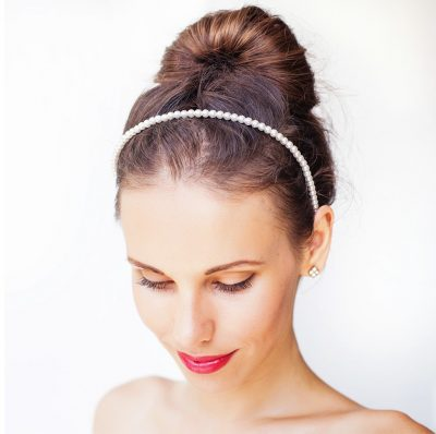 Women wears a sleek top knot bun hairstyle for the holidays, with a pearl headband