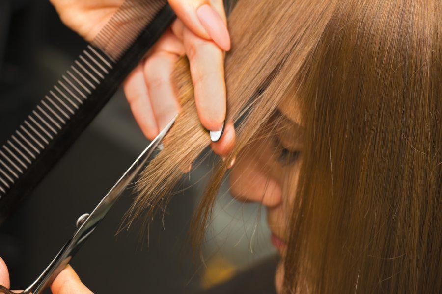 A closeup of a woman getting her bangs cut