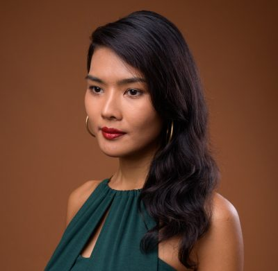 asian woman green dress brown background retro glamorous waves holiday hair ideas for 2019 viviscal hair blog