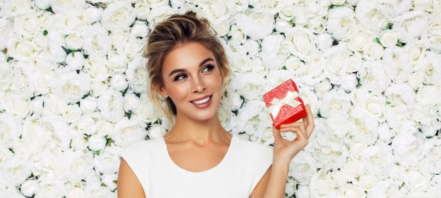 smiling blonde woman holding small red gift white flowers background holiday hair ideas for 2019 viviscal hair blog