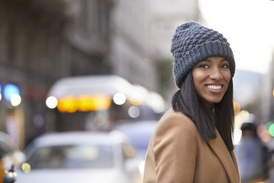 smiling african american woman gray knit hat straight hair city street does wearing a hat thin your hair? viviscal hair blog
