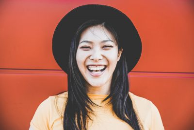 laughing asian woman closeup black fedora hat orange red wall background does wearing a hat thin your hair? viviscal hair blog