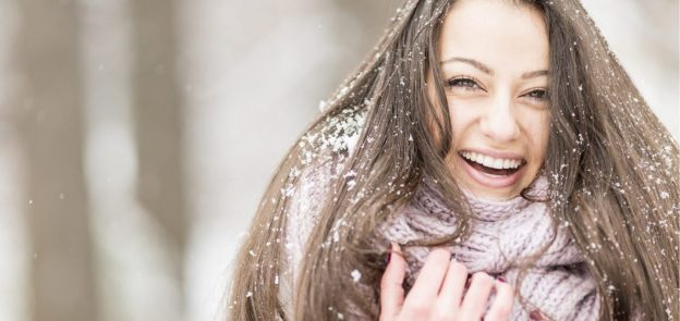 laughing smiling woman outside snow winter long hair pink scarf how to care for your hair this winter viviscal hair blog