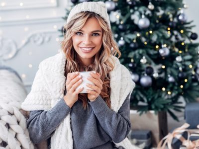 woman long blonde wavy hair christmas tree cup hot drink does wearing a hat thin your hair? viviscal hair blog
