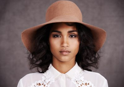 fashionable african american woman curly hair tan floppy hat does wearing a hat thin your hair? viviscal hair blog