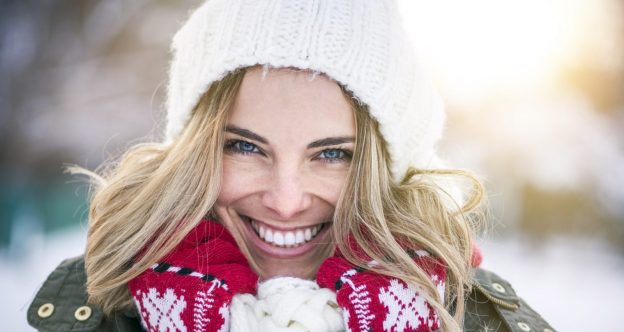 smiling woman white winter hat blonde hair red white wool scarf winter snowy background top winter hair colors for blondes viviscal hair blog