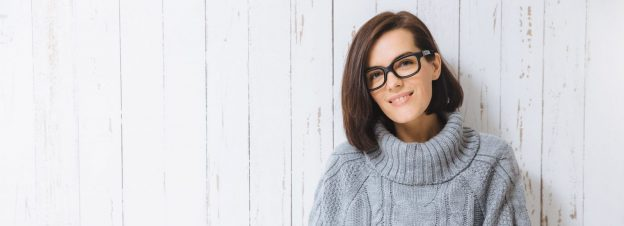 smiling woman short dark brown bob haircut black glasses gray turtleneck sweater white painted wall background how to wear and style chin length bobs viviscal hair blog