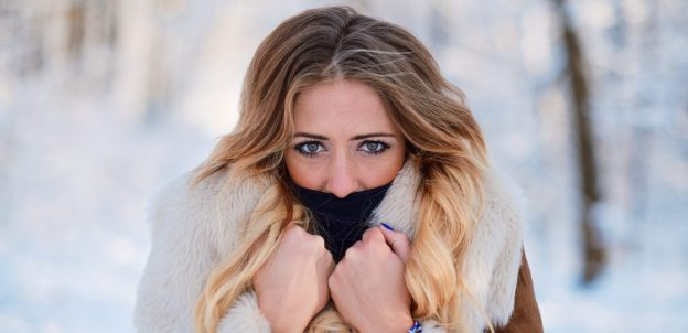 woman cold outside winter snow covering mouth black collar blonde dyed hair best dry hair treatments viviscal hair blog